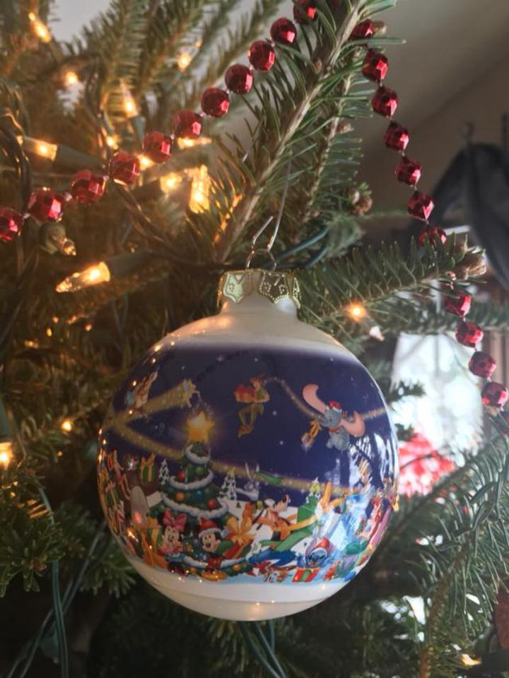 A Christmas ornament ball with a Disney scene painted on it.