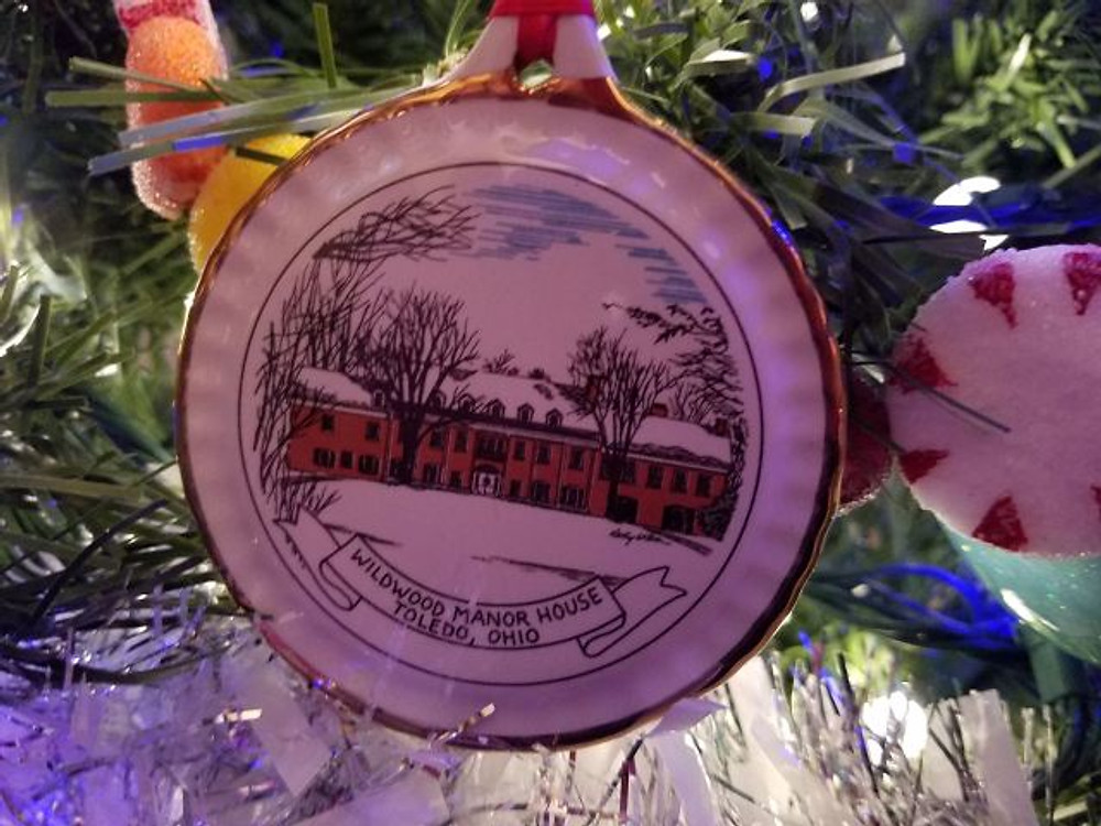 A picture of a plate shaped ornament that has a picture of the Manor House in a snowy scene.