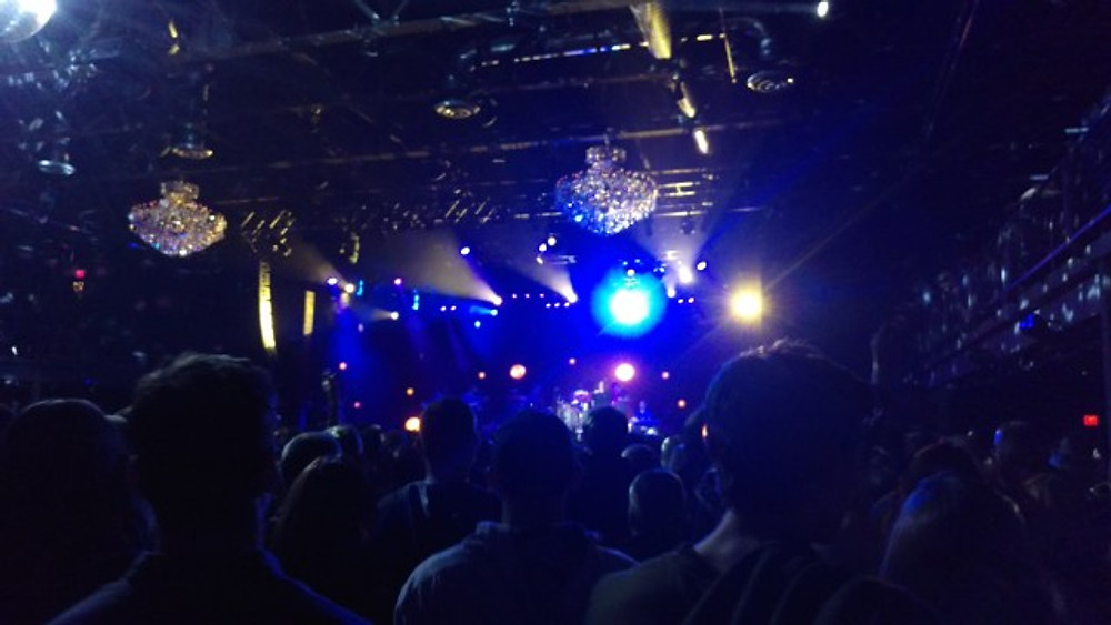 A picture from the back of the room of the crowd with the band on the stage in the distance.