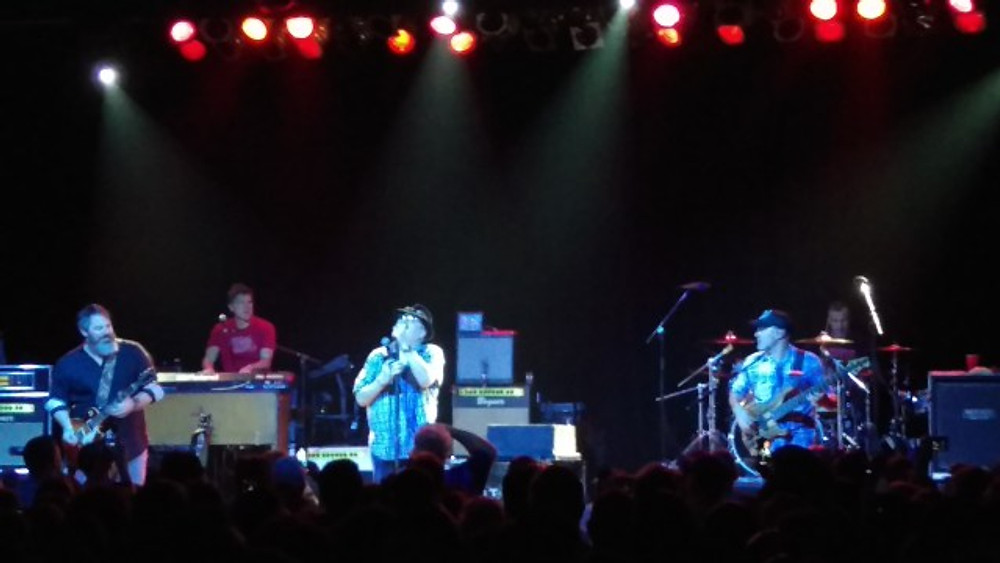 A picture of Blues Traveler on stage. John Popper is in his signature hat.