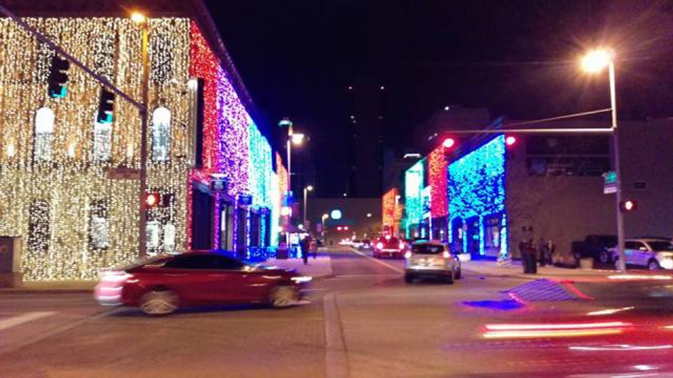 A picture of some buildings in downtown Toledo decordated with lots of holiday lights.