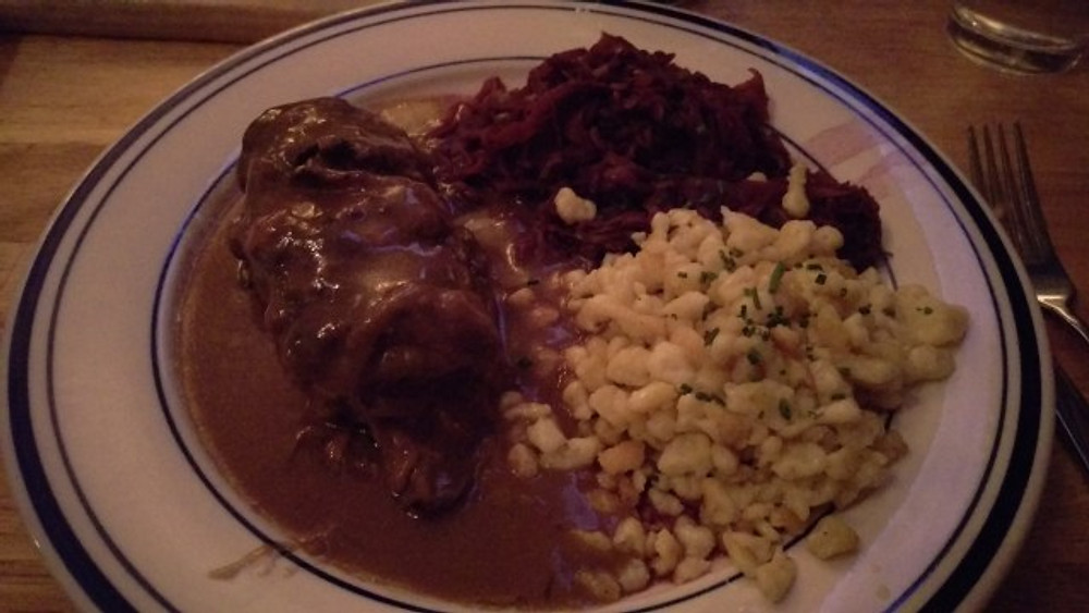A picture of a plate of beef rouladen, spatzle and red cabbage.