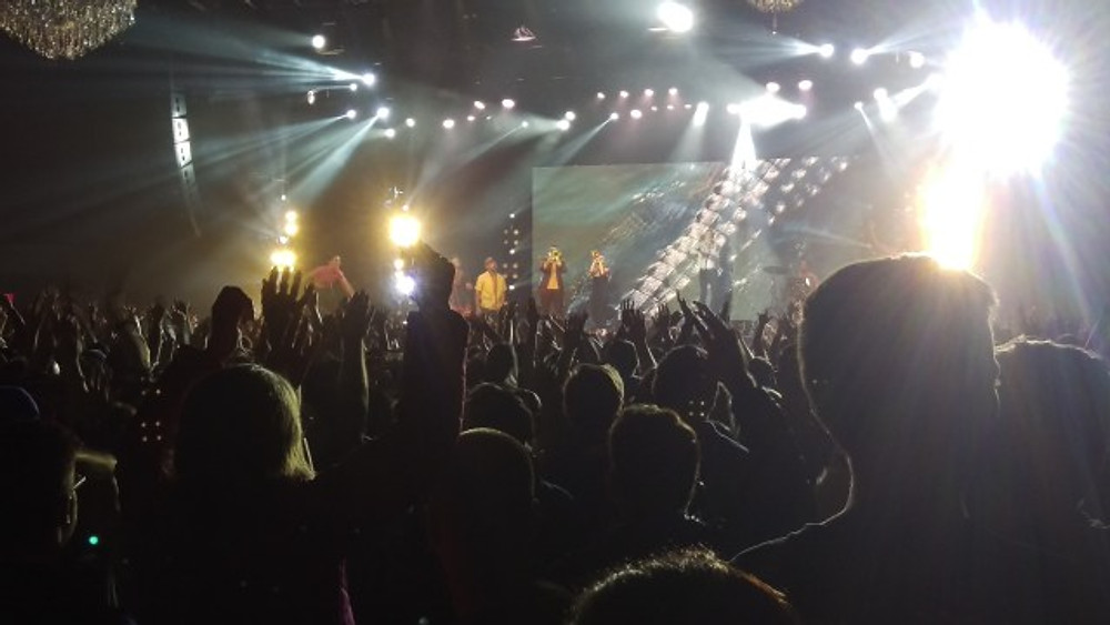 A picture of the crowd with their hands up in the air.