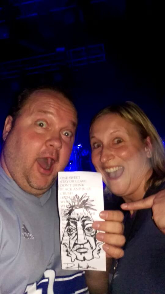 A picutre of my husband and I holding a set list we got in Berlin. Dave had doodled a drawing of faces on it.