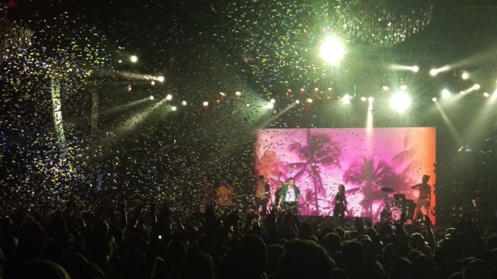 A picture of Macklemore on stage with confetti coming down through the lights.