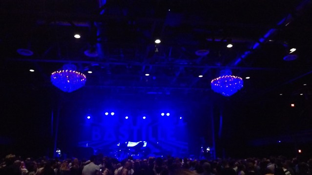 A view of the stage from the back of the room with the chandeliers hanging.