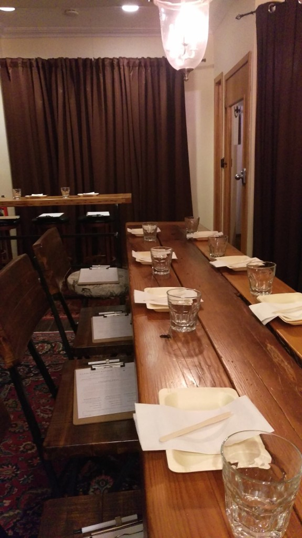 A picture of a long wooden table with several place setting set out.