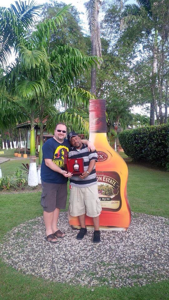 My husband and our friend holding his bottle of Appleton rum standing in front of a giant rum sign at Appleton Estates.