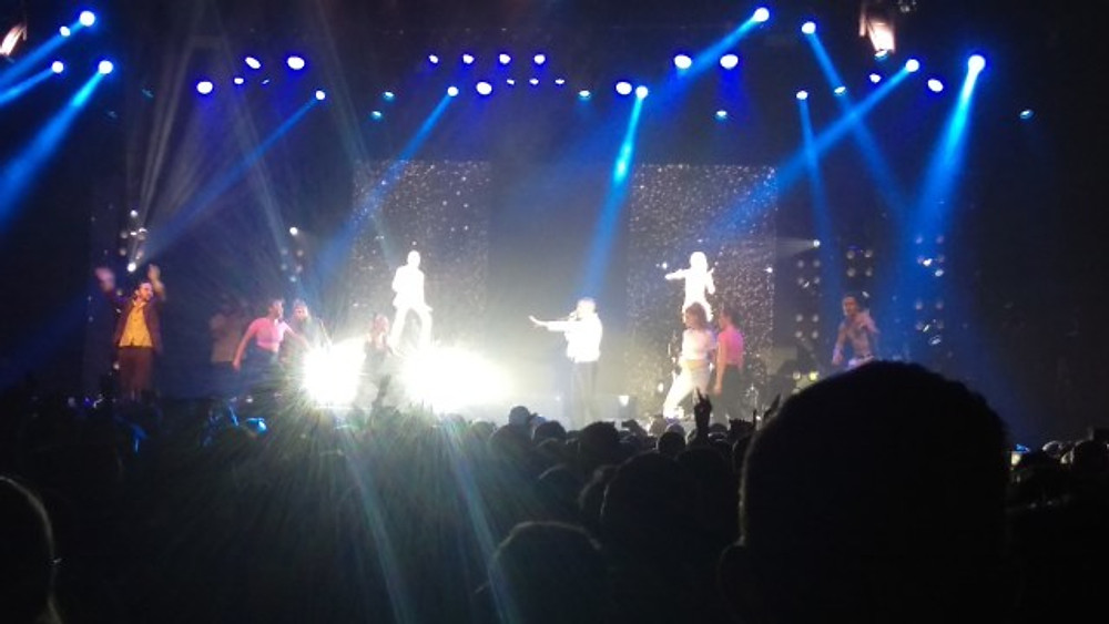 A picture of Macklemore, his dancers and two fans having a dance off.