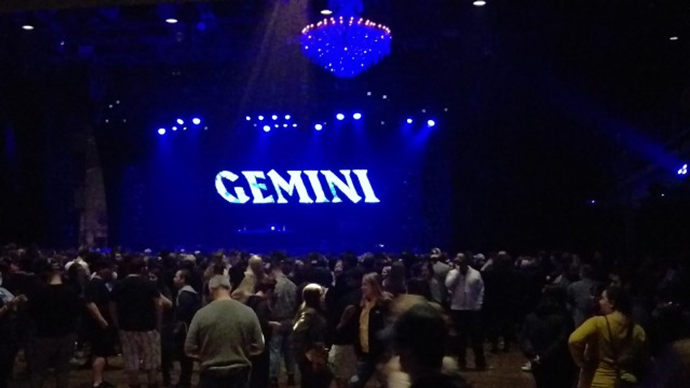 A picture from the back of the room of the crowd and an empty stage, with Gemini lit up on the screen.