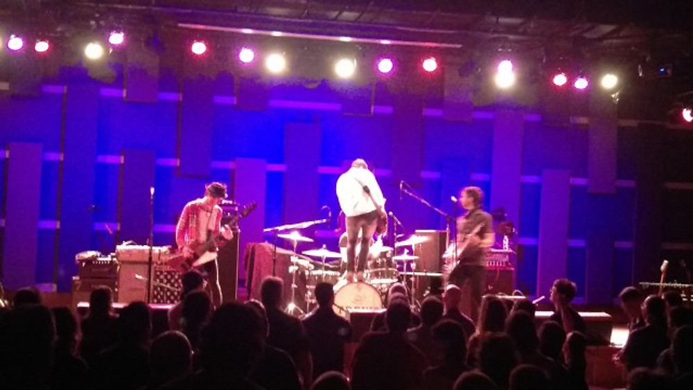 A picture of The Trews on stage with their guitarist standing on top of the drum set.