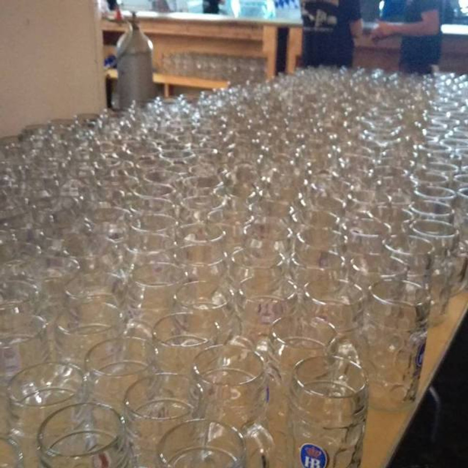A picture of dozens of glass liter beer mugs sitting on a table waiting to be filled.