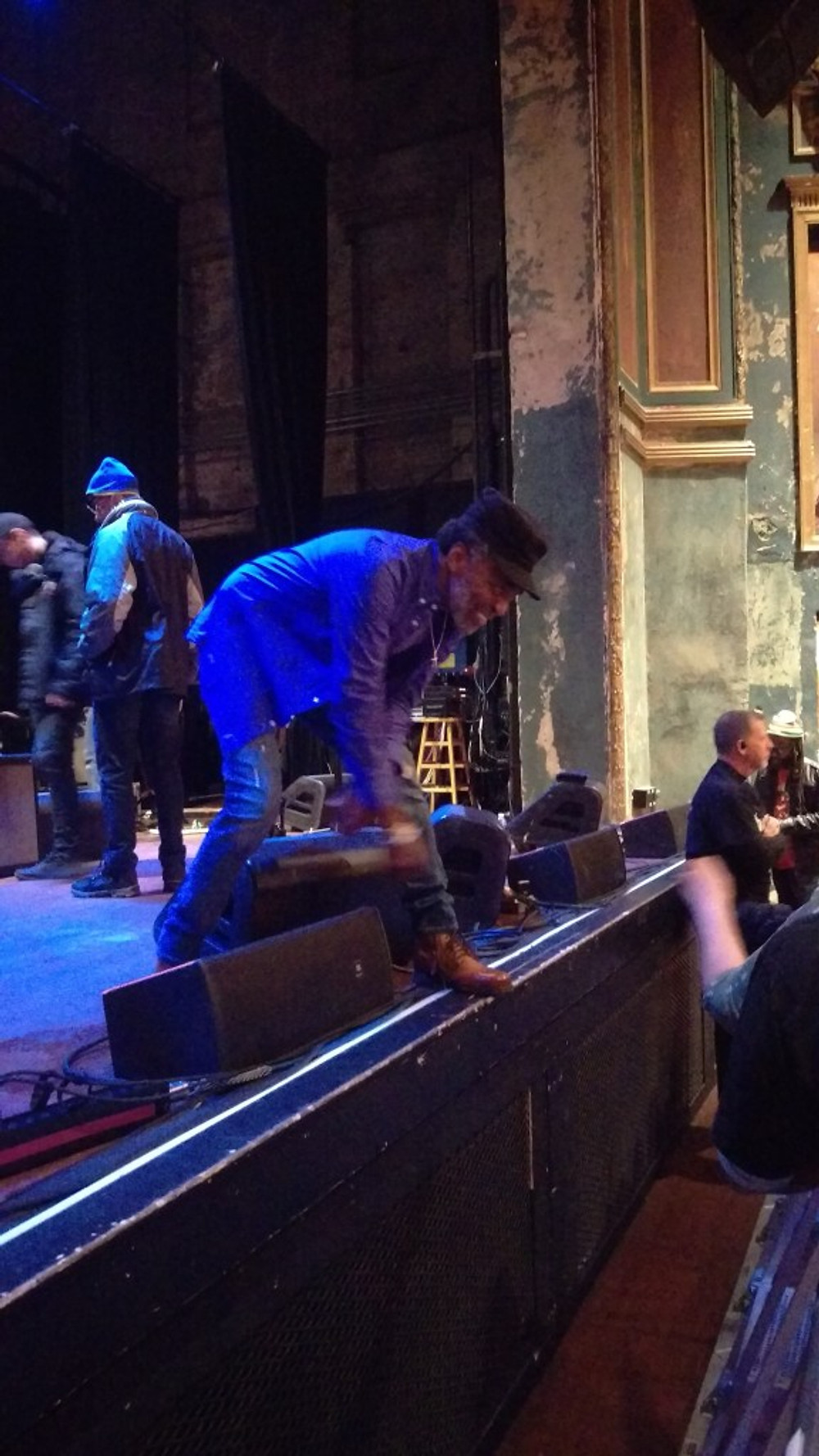 Donald Kinsey leaning over the stage to shake a fan's hand.
