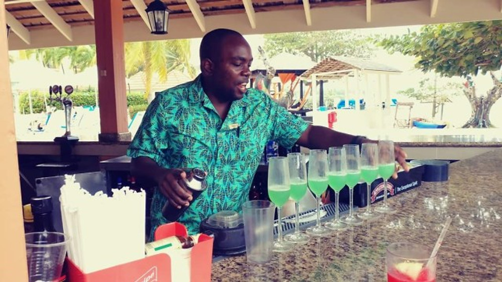 A picture of one of the bartenders making drinks at the bar.