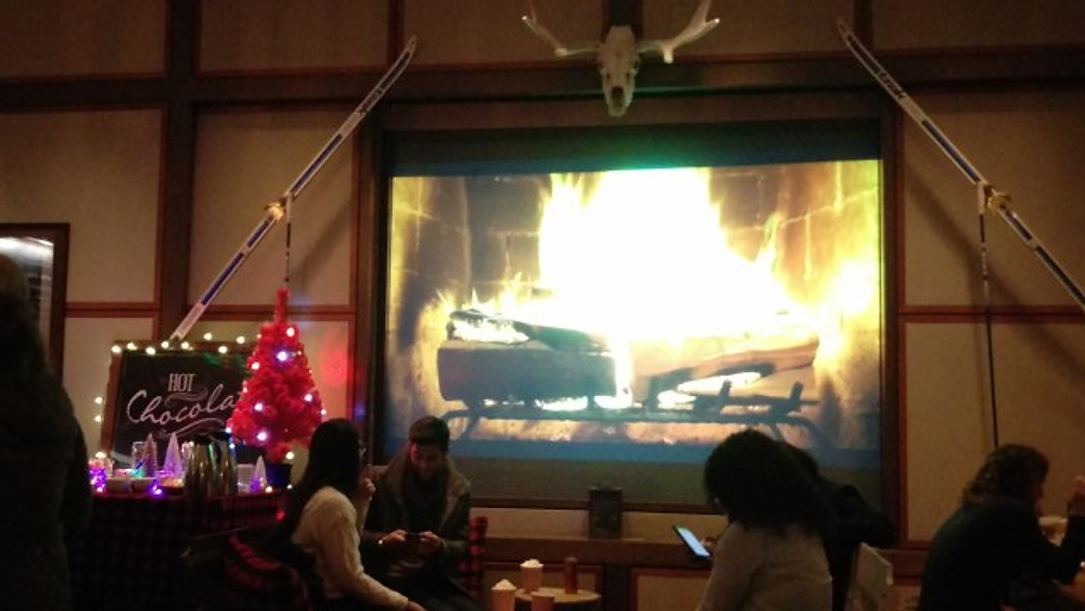 A picture of the hot chocolate bar area at SkyGarten, as well as the video screen showing a roaring fire in the fireplace.