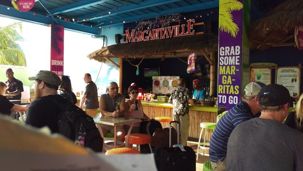 A picture of the Margaritaville bar on the outside of the airport with people sitting around and having drinks.
