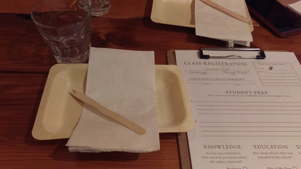 A picture of a place setting with a plate, wooden fork, napkin, small empty glass, and a page on a clipboard to take notes.