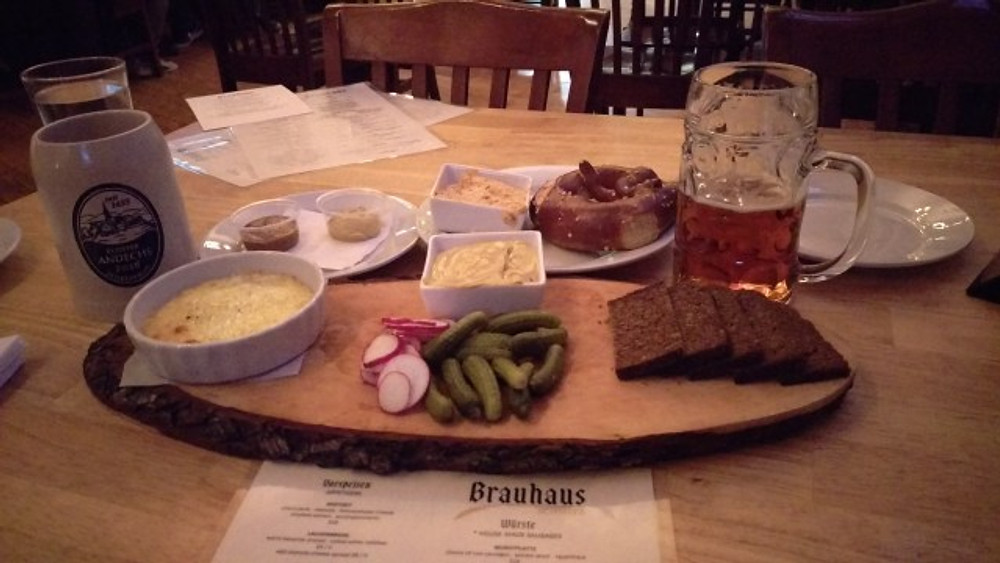 A picture of a wooden board with a cheese dip, pickles, bread, radishes, mustard and a pretzel. Plus two beers.