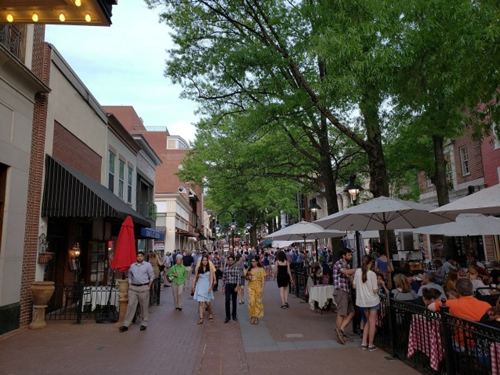 The Charlottesville downtown mall area during the summer, with people walking down the pedistrian walkway.