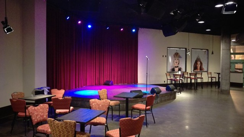 The upstairs room with the stage and a couple of tables and chairs.