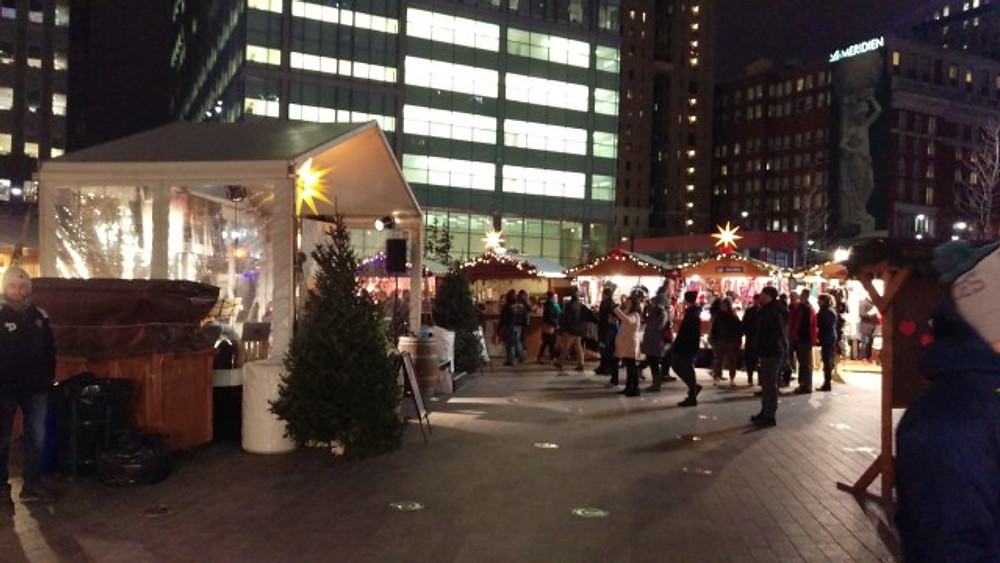 A picture of the center court area of the Christmas Village with a tent covering a stage area.