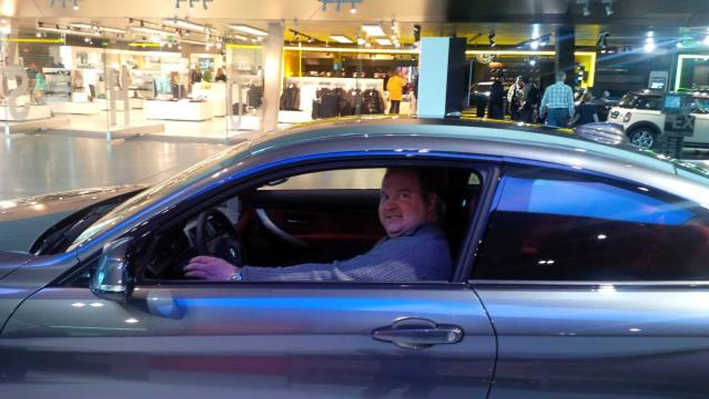 A picture of my husband sitting in a BMW.