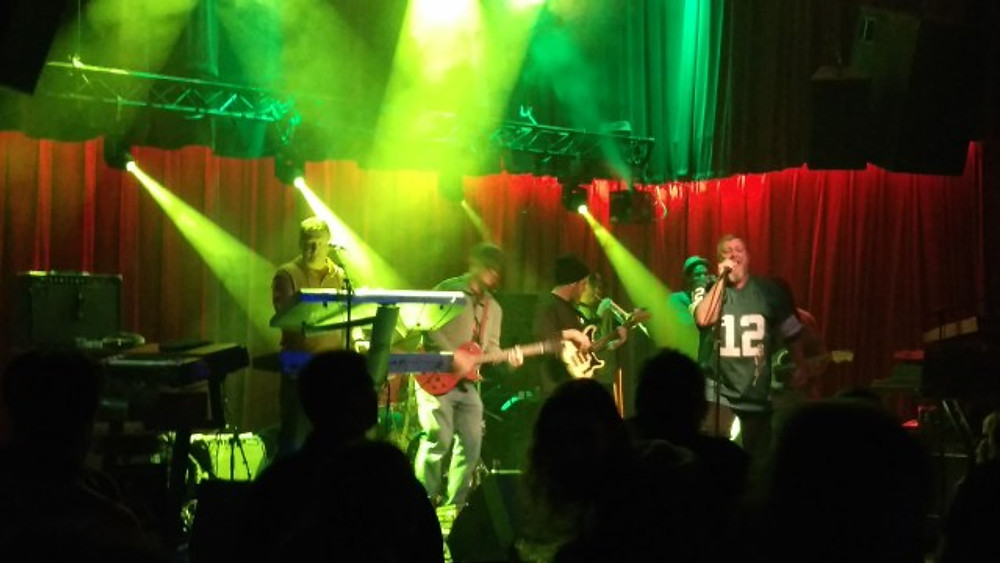Jah Works on stage at The Ardmore Music Hall. The lead singer is wearing a Randall Cunningham jersey.