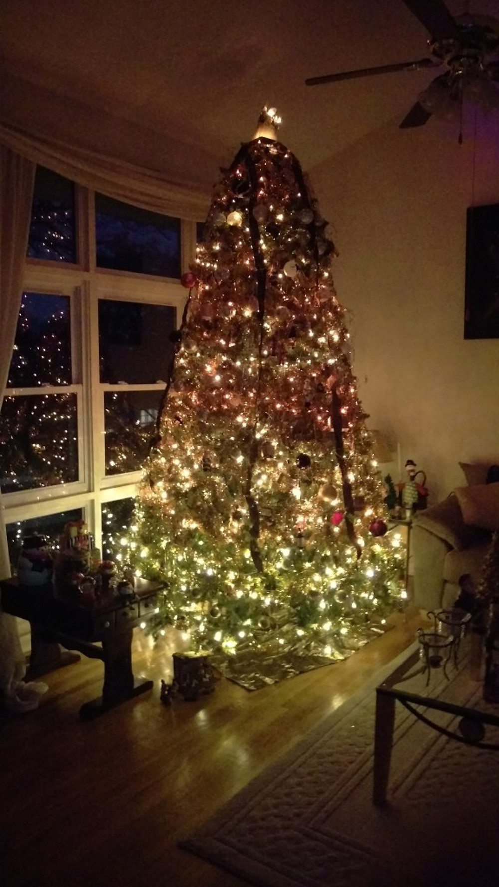 A picture of my Christmas tree lit up. The tree is decorated in gold and white lights and stands about 10 feet tall.