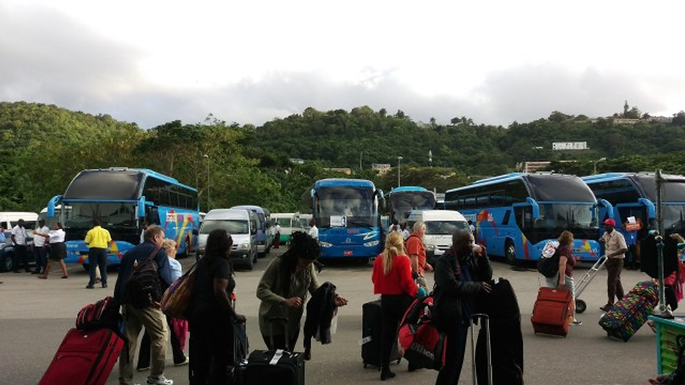 A picture of travelers taking their luggage to the shuttle buses lined up at the airport exit.