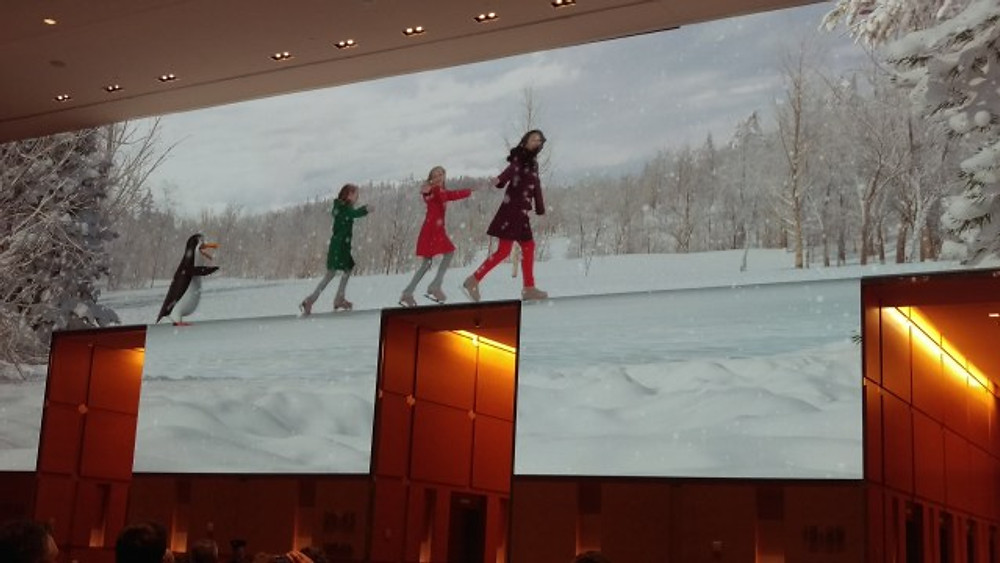 A pictures of ice skaters with a penguin on the screen at the Comcast Center.