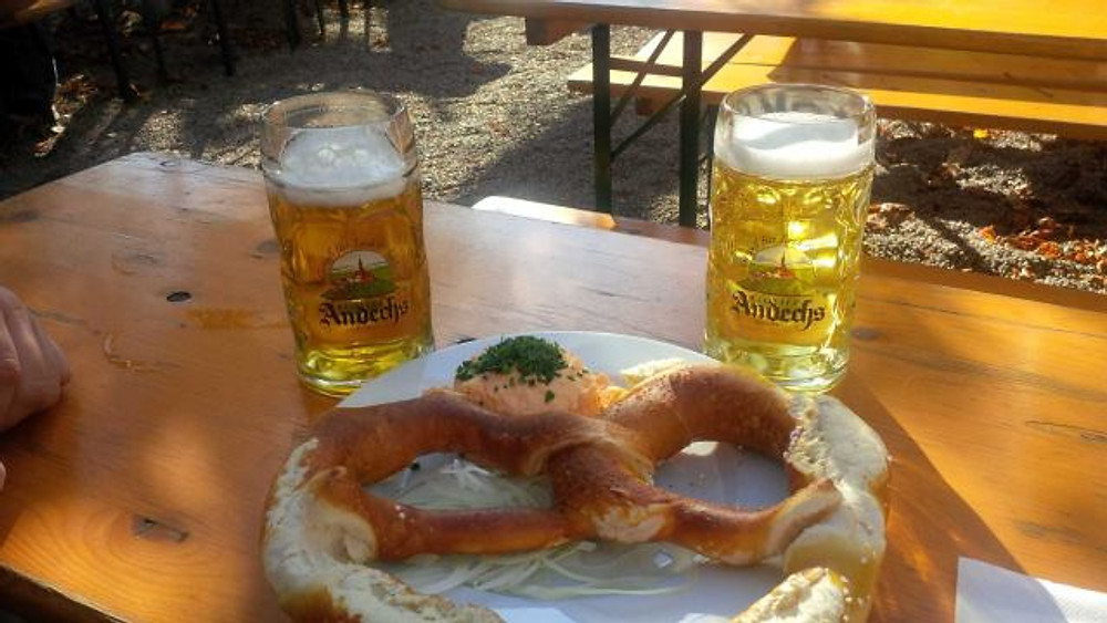 A picture of a giant pretzel on a plate and two beers.