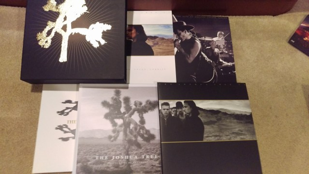 A picture of the various record albums and books you get in the Joshua Tree Deluxe 7 LP Set.