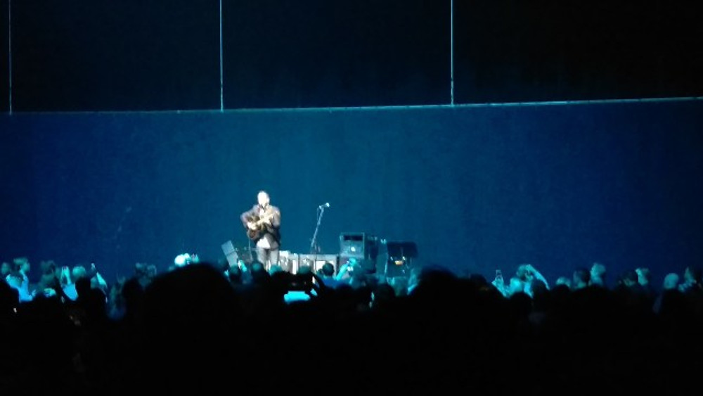 Dave Matthews on the stage singing and playing guitar.