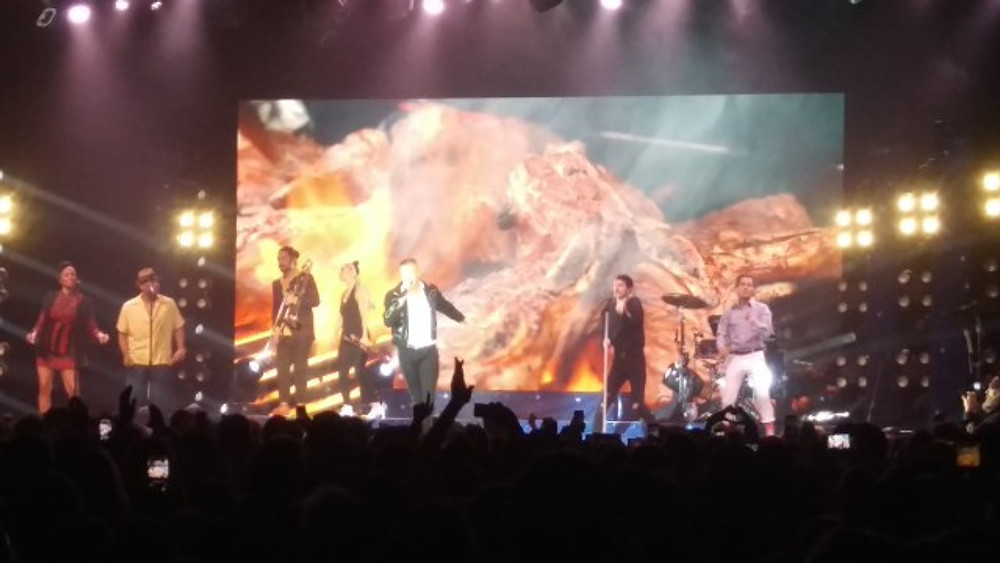 A picture of Macklemore and his musicians on stage with a large video screen behind them.