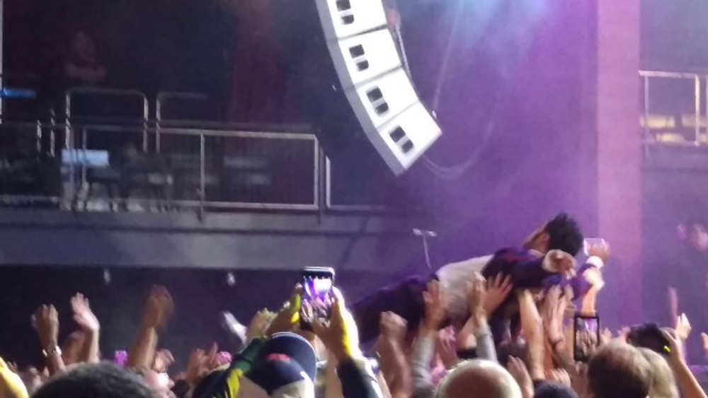 This is a picture of the lead singer of Vintage Trouble crowd surfing during their set.