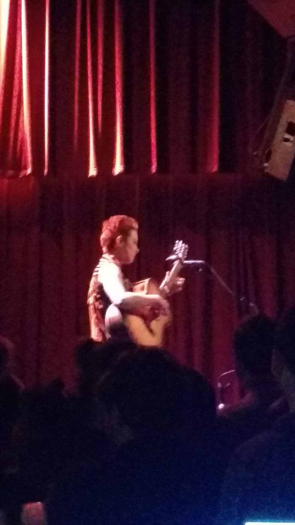 A picture of Christie Lenee on stage with her guitar.