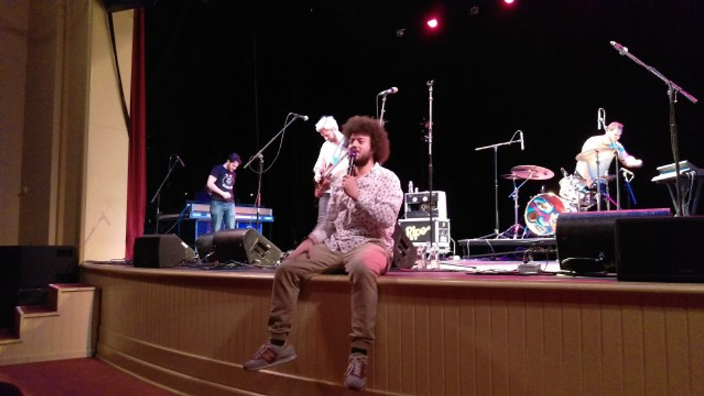 A picture of the lead singer sitting on the edge of the stage.