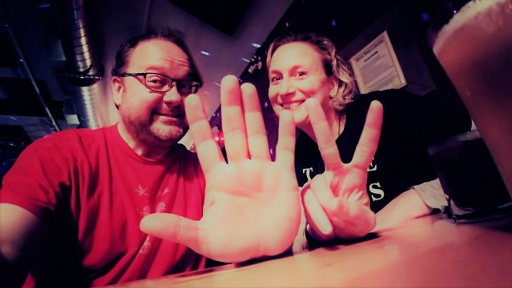 A picture of my husband and I holding up 5 and 2 fingers to show concert number 52.