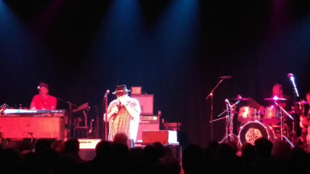A picture of John Popper playing the harmonica during their set.