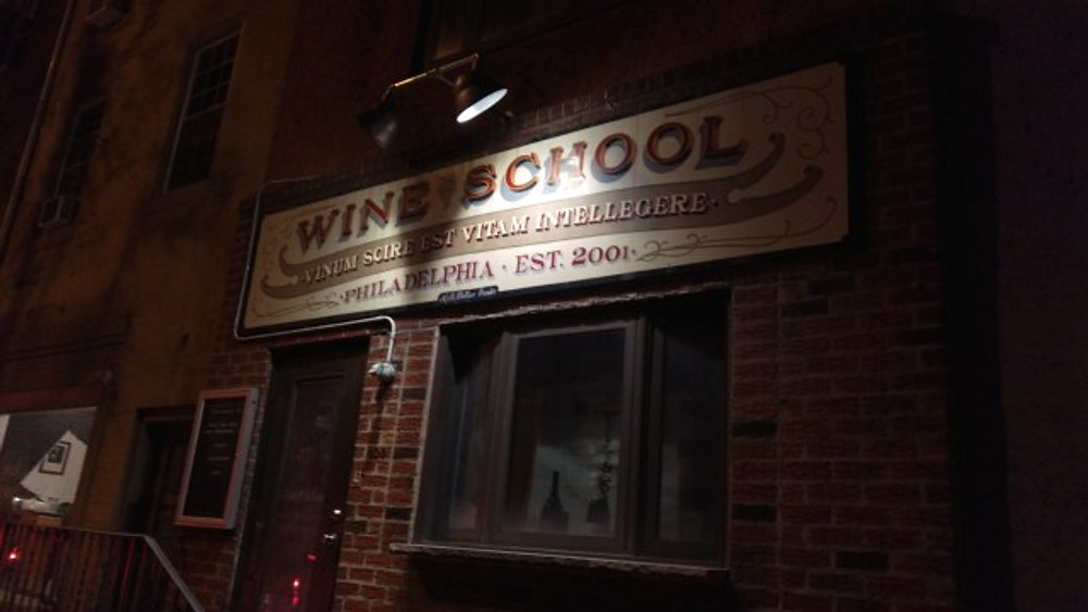 A picture of the outside of the wine school with a light shining on the sign.