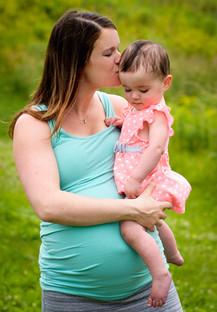 Pregnant Mom Kissing Baby Girl