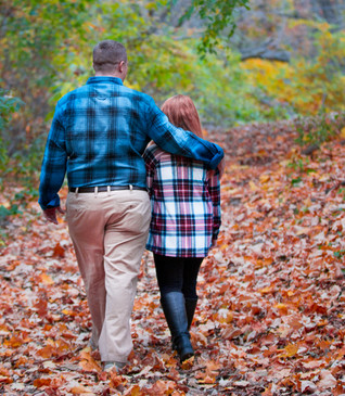 Dad Walking with young daughter through leaves