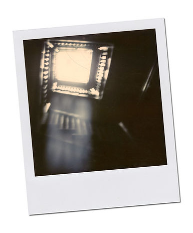 Polaroid photo of skylight and staircase by Loren
