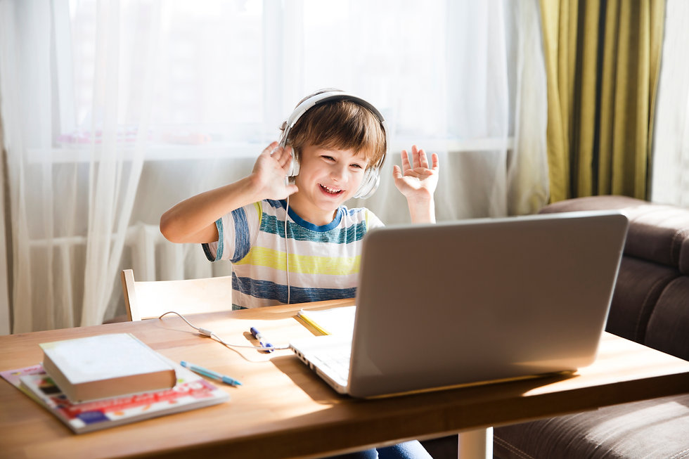 child boy in headphones is using a laptop and study online with video call teacher at home...ing.jpg