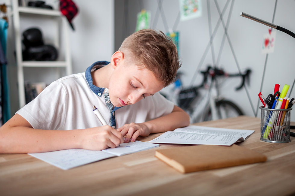 Focused preteen boy doing homework on desk in his room.jpg