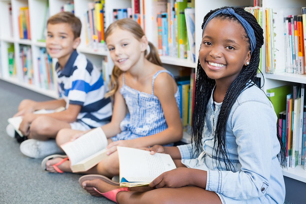 Portrait of smiling school kids sitting on floor and reading book in library.jpg