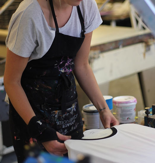 A woman preparing a white t-shirt to be screen-printed, by pulling it onto a printing board.