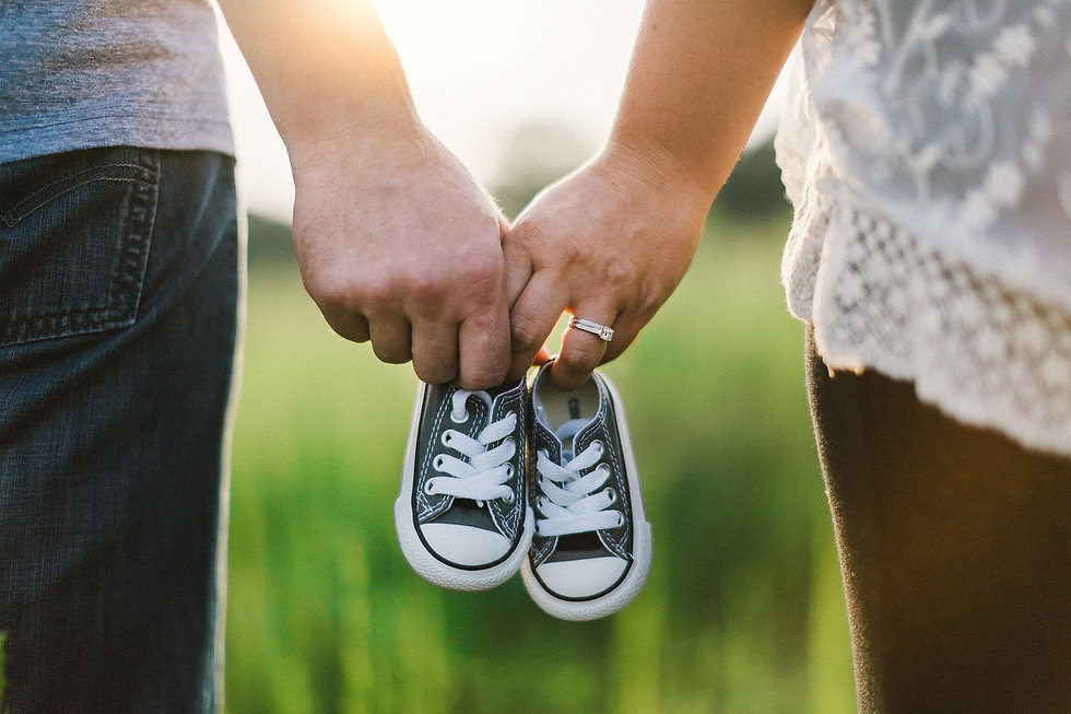 Man and women holding little kids shoes to represent life insurance importance