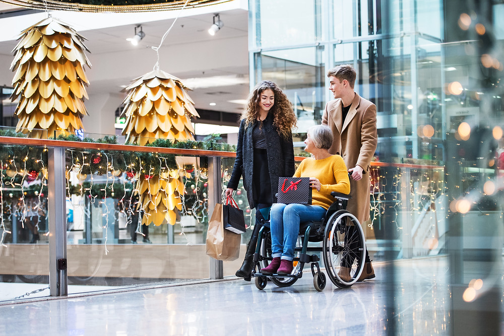 Two children, male and female, and their grandmother, who is using a wheelchair pushed by the male grandchild, as they stroll through a shopping center decorated with holiday decor.