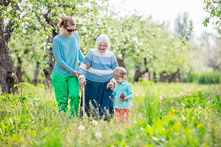 Family members assisting elderly lady in walking with cane outdoors through a spring meadow